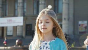 Mooie weinig blonde open ogen en glimlachen bij camera op een stadsgebied stock video