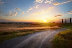 Mooie windende landweg die door landelijk platteland leiden stock afbeeldingen