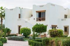 Mooie witte die huizen door groene struiken en bloemen worden omringd stock afbeelding