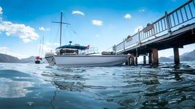 Mooie witte die jacht en boot bij lange houten pijler op zee wordt vastgelegd stock foto