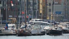 Mooie witte jachten met golvende die vlaggen in de haven van Gdansk, watervervoer worden geparkeerd stock videobeelden