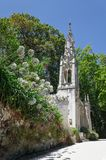 Mooie witte kapel onder bloeiende bloemen in groen park Stock Afbeelding