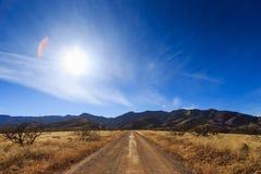 Mooie woestijnweg met zon glanzen helder in de blauwe hemel royalty-vrije stock foto