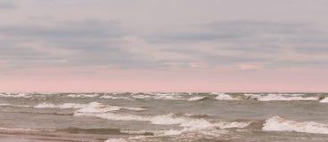 Mooie wolken en roze gloeiende hemel over veranderlijke golven stock fotografie