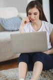 Mooie ypungvrouw die laptop thuis met behulp van Stock Afbeeldingen