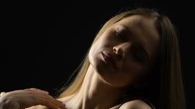 Mooie zelfverzekerde jonge vrouw wat betreft hals, die van, sensualiteit genieten stock video