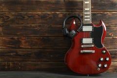 Mooie zes - koord elektrische gitaar met hoofdtelefoons tegen houten achtergrond stock foto