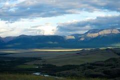 Mooie zonnige vallei tussen bergen met weelderige wolken Royalty-vrije Stock Afbeeldingen