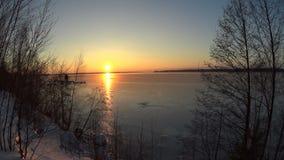 Mooie zonsondergang bij bevroren rivier in de winter stock video
