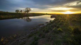 Mooie zonsondergang bij de rivier in het dorp Stock Afbeelding