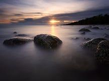 Mooie zonsondergang bij het steenstrand royalty-vrije stock foto
