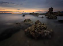 Mooie zonsondergang bij het steenstrand stock afbeeldingen