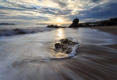 Mooie zonsondergang bij het steenstrand stock foto's