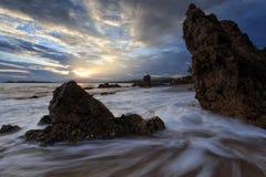 Mooie zonsondergang bij het steenstrand royalty-vrije stock foto's