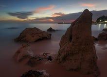 Mooie zonsondergang bij het steenstrand stock foto