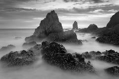 Mooie zonsondergang bij het steenstrand in zwart-wit stock afbeeldingen