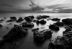 Mooie zonsondergang bij het steenstrand in zwart-wit royalty-vrije stock afbeeldingen