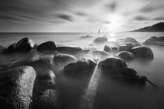 Mooie zonsondergang bij het steenstrand in zwart-wit stock foto's
