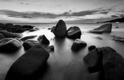 Mooie zonsondergang bij het steenstrand in zwart-wit stock fotografie