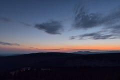 Mooie zonsondergang in de bergen met verlicht plattelandshuisje stock fotografie