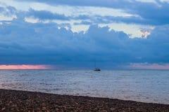 Mooie zonsondergang met heldere wolken boven het overzees De kust is gestippeld met kiezelstenen en een varend schip royalty-vrije stock afbeeldingen
