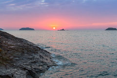Mooie zonsondergang op een rotsachtige overzeese kustaard Stock Fotografie