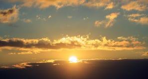 Mooie zonsondergang op hemel De gouden zon verlicht de wolken De zon is in het midden Stock Foto's