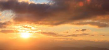 Mooie zonsondergang op hemel De gouden zon verlicht de wolken over bergen De zon is op de linkerkant Royalty-vrije Stock Afbeeldingen