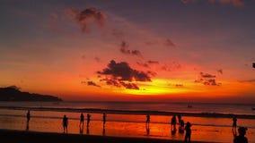 Mooie zonsondergang op het strand van het Jimbaran-dorp met silhouetten van mensen Bali, Indonesië stock video
