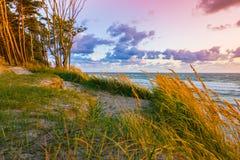 Mooie zonsondergang op Oostzee met kleurrijke bewolkte gouden hemel, stock fotografie