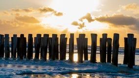 Mooie Zonsondergang over golfbrekers in Zeeland stock foto's