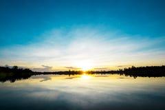 Mooie zonsondergang over meer met blauwe hemel Royalty-vrije Stock Afbeelding