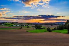 Mooie zonsondergang over plattelandslandschap van rollende heuvels met zonstralen die hemel doordringen en helling aansteken Royalty-vrije Stock Foto's