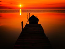 Mooie zonsondergang over water en silhouet van vissersboot Royalty-vrije Stock Afbeeldingen