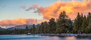 Mooie zonsondergangmeningen van de oever van Zuidenmeer Tahoe, huizen zichtbaar onder pijnboombomen stock foto's