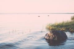 Mooie zonsopgang in het overzees bij het wilde strand wijnoogst stock fotografie