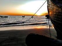 Mooie zonsopgang over een oude houten vissersboot op een kiezelsteenstrand stock afbeelding