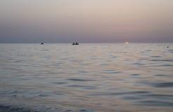 Mooie zonsopgang over het overzees, de vissers in een boot Stock Afbeelding