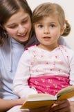 Mooie zusters die boek lezen Stock Afbeeldingen