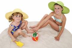 Mooie Zusters die in de Hoeden van het Strand in het Zand spelen royalty-vrije stock afbeelding