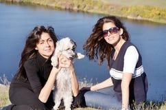 Mooie zusters die van de tijd genieten die met hun kleine hond wordt doorgebracht Royalty-vrije Stock Foto