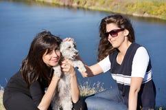 Mooie zusters die van de tijd genieten die met hun kleine hond wordt doorgebracht Royalty-vrije Stock Afbeeldingen