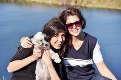 Mooie zusters die van de tijd genieten die met hun kleine hond wordt doorgebracht Stock Foto's