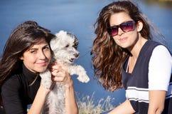 Mooie zusters die van de tijd genieten die met hun kleine hond wordt doorgebracht Royalty-vrije Stock Fotografie