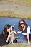 Mooie zusters die van de tijd genieten die met hun kleine hond wordt doorgebracht Stock Afbeeldingen