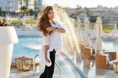 Mooie zwangere vrouw die met elegant haar in een wit overhemd glimlachen stock afbeeldingen