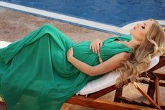 Mooie zwangere vrouw met blond haar in elegante kleding Stock Foto's