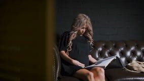 Mooie zwangere vrouw in zwarte kledingszitting op de grote bruine laag die haar buik strijken zacht en tijdschrift lezen stock videobeelden