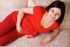 Mooie zwangere vrouwenzitting op de laag Royalty-vrije Stock Foto's