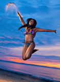 Mooie zwarte Afrikaanse Amerikaanse vrouw die op het strand bij s springen Stock Fotografie
